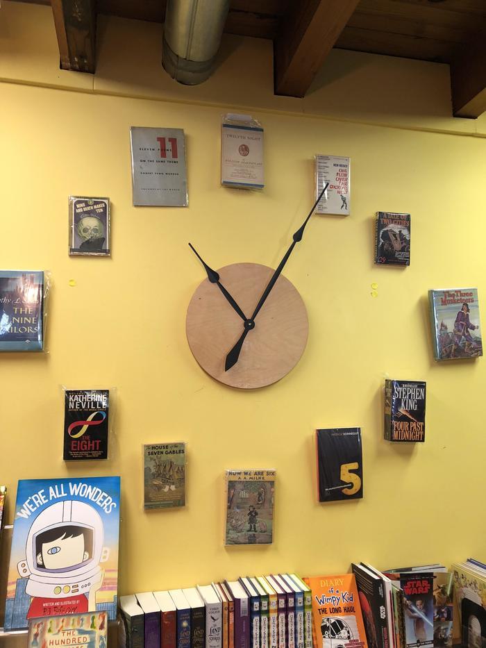 Часы в книжном магазине, сделанные из книг с соответствующими названиями
