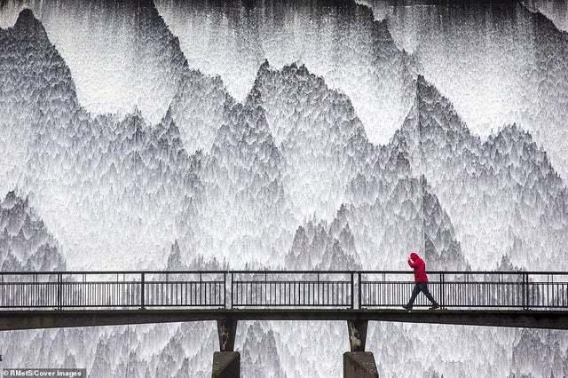 Это не странный пейзаж за мостом, а потоки воды стекающие по почти вертикальной стене плотины