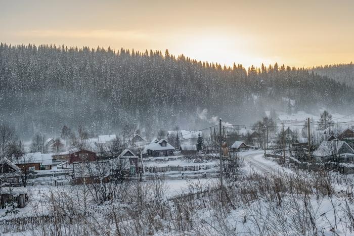 Морозным вечером жители посёлка Усьва топят избы